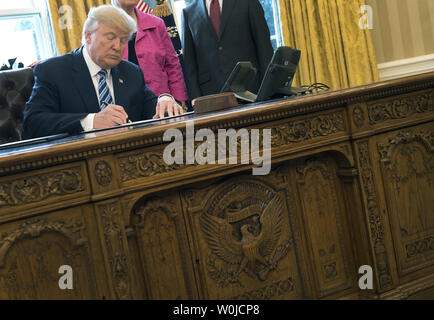 President Donald Trump signs a series of three Executive Actions that, according to Trump, will 'restore safety in America,' after swearing-in Attorney General Jeff Sessions (R), in the Oval Office at the White House in Washington, D.C. on February 9, 2017. Sessions wife Mary also attended.  Photo by Kevin Dietsch/UPI - Stock Photo
