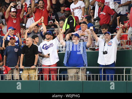Chicago Cubs fans  celebrate a ruling from MLB that there was no fan interference with Anthony Rizzo's two run home run in the fourth inning against the Washington Nationals in game 2 of the NLDS at Nationals Park in Washington, D.C. on October 7, 2017.  The fan at lower right holds the HR ball.   Photo by Pat Benic/UPI - Stock Photo
