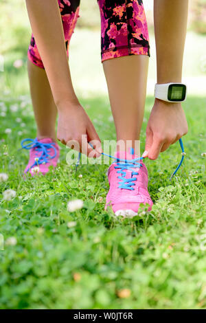 Weight loss - runner tying laces wearing smartwatch heat rate monitor and activity tracker for cardio exercise. Woman getting ready for jogging workout. Closeup of running shoes. - Stock Photo
