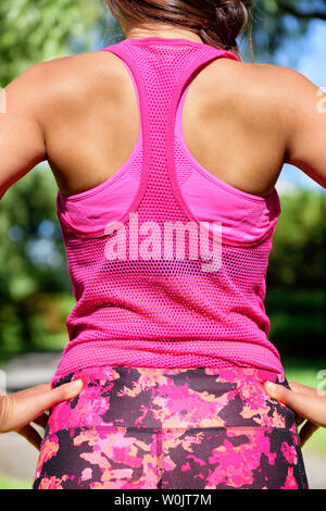 Woman runner in mesh tank top activewear and floral leggings. Female runner after workout. - Stock Photo