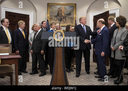 President Donald Trump shakes hands as he arrives for a signing ceremony for Space Policy Directive - 1, in the Roosevelt Room at the White House on December 11, 2017 in Washington, D.C. Trump was joined by members of the Space Council, Cabinet officials, congressional members and industry leaders. The directive assigns the NASA to initiate a space to return American astronauts back to the Moon, and eventually to Mars. Photo by Kevin Dietsch/UPI - Stock Photo