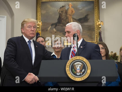 President Donald Trump shakes hands with Vice President Mike Pence after delivering remarks before Trump signed Space Policy Directive 1, in the Roosevelt Room at the White House on December 11, 2017 in Washington, D.C. Trump was joined by Vice President Mike Pence (R) and retired  Astronaut Jack Schmitt (L). The directive assigns the NASA to initiate a space to return American astronauts back to the Moon, and eventually to Mars. Photo by Kevin Dietsch/UPI - Stock Photo