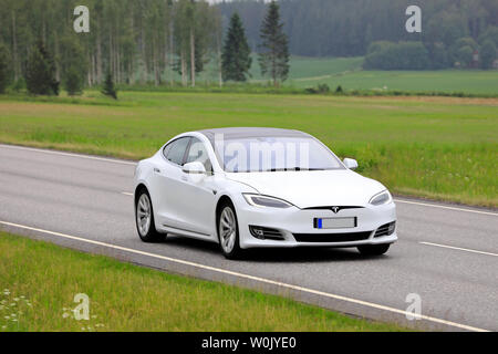 Salo, Finland. June 14, 2019. White Tesla Model S electric car driving at speed on rural highway through Finnish countryside in the summer. - Stock Photo