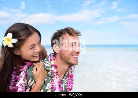 Beach couple having fun piggybacking and laughing on Hawaii travel holiday. Beautiful Asian mixed race woman piggybacking on Caucasian boyfriend wearing traditional Hawaiian lei on Oahu, Hawaii, USA. - Stock Photo