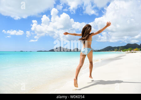 Travel, beach and vacation holidays concept with bikini girl happy running full of joy and aspiration on pristine beautiful Caribbean beach with turquoise water. Woman in bikini having fun. - Stock Photo