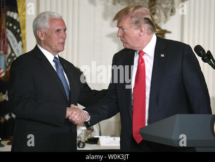President Donald Trump (R) shakes hands with Vice President Mike Pence after concluding remarks, as he hosts the National Space Council in the East Room of the White House, June 18, 2018, in Washington, DC. Trump signed a directive to reform and modernize US commercial space policy.                                  Photo by Mike Theiler/UPI - Stock Photo