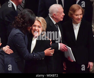 Hillary Clinton hugs Michelle Obama as former presidents and spouses assemble at the funeral of President George H.W. Bush at the National Cathedral in Washington D.C. on December 5, 2018. At right ,Jimmy Carter and his wife Rosalynn talk.      Photo by Kevin Dietsch/UPI - Stock Photo