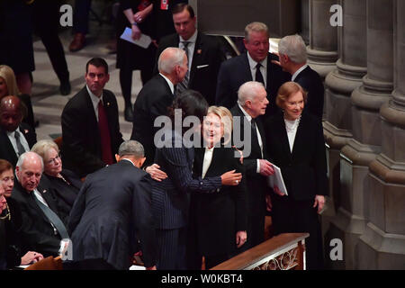 Hillary Clinton hugs Michelle Obama as former presidents and spouses assemble at the funeral of President George H.W. Bush at the National Cathedral in Washington D.C. on December 5, 2018. At right, Jimmy Carter and his wife Rosalynn talk in front of Bill Clinton chating with Al Gore.  Photo by Kevin Dietsch/UPI - Stock Photo