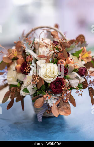 Home festive flower arrangement from leaves, roses, berries. Autumn holidays - Stock Photo