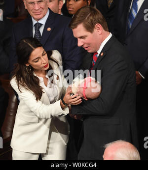 Rep. Alexandria Ocasio-Cortez (D-NY) chats with Rep. Eric Swalwell (D-CA) has he holds his new daughter Kathryn Watts Swalwell at the 116th U.S. Congress in the House Chamber on Capitol Hill in Washington, DC on January 3, 2019. Swalwell's daughter was born last October 24.   Photo by Pat Benic/UPI - Stock Photo
