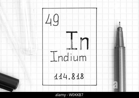 The Periodic table of elements. Handwriting chemical element Indium In with black pen, test tube and pipette. Close-up. - Stock Photo