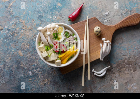 Noodle with mushrooms and vegetables in bowl. Chili, yellow paprika, tofu, onion, boiled beef and Chinese mushrooms on concrete background. Top view f - Stock Photo