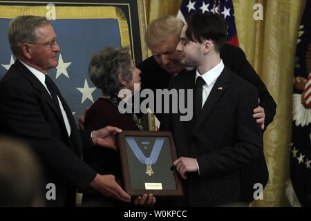 U.S. President Donald Trump presents the Medal of Honor posthumously to Army Staff Sergeant Travis Atkins for conspicuous gallantry during an event at the White House in Washington on March 27, 2019. Trevor Oliver, son of Staff Sergeant Atkins, accepts the award and commemorates his father's selfless service and sacrifice. Photo by Yuri Gripas/UPI - Stock Photo