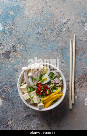 Hot soup with noodle, chili, tofu, green onion and mushrooms in dish with sticks on concrete blue background. Vertical top vie - Stock Photo