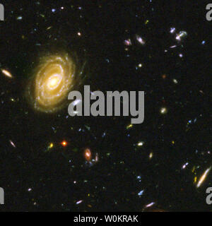 This close-up snapshot of galaxies in the Hubble Ultra Deep Field reveal the drama of galactic life. Ut shows a majestic spiral galaxy, one of the nearest galaxies in the Ultra Deep Field. This galaxy existed about 1 billion years ago, when the cosmos was 13 billion years old.  The galaxies in this photo were plucked from a harvest of nearly 10,000 galaxies in the Ultra Deep Field, the deepest visible-light image of the cosmos. Photo released March 9, 2004.   (UPI Photo/NASA/Hubble) - Stock Photo