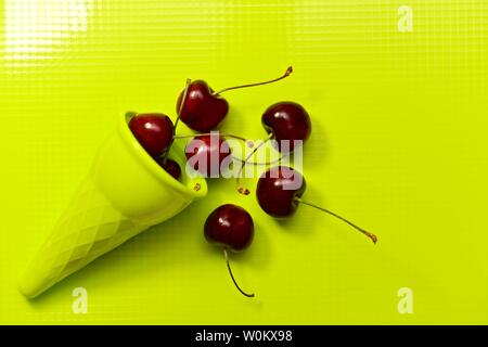 Dark red sweet cherry sprinkled from a green plastic waffle cone on a light green plastic glossy background. View from above.