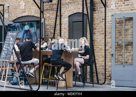 London, UK - June 22, 2019: People enjoying food and drinks at Rapha cafe inside Spitalfields Market, one of the finest Market Halls in London with st - Stock Photo
