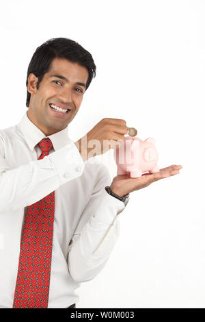 Indian businessman inserting a coin into a piggy bank - Stock Photo