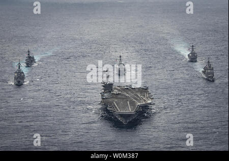 The Nimitz-class aircraft carrier USS Carl Vinson (CVN 70) leads the Japan Maritime Self-Defense Force destroyers JS Ashigara (DDG 178), left front, and JS Samidare (DD 106), left rear, the Arleigh Burke-class guided-missile destroyers USS Michael Murphy (DDG 112), center rear, and USS Wayne E. Meyer (DDG 108), right rear, and the Ticonderoga-class guided-missile cruiser USS Lake Champlain (CG 57), right front, during a transit the Philippine Sea on April 28, 2017. The U.S. Navy has patrolled the Indo-Asia-Pacific routinely for more than 70 years promoting regional peace and security. Photo by - Stock Photo