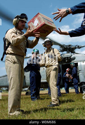 U.S. Navy personnel load bags of rice and other humanitarian supplies onto an SH-60B Seahawk helicopter, assigned to the 'Saberhawks' of Helicopter Anti-Submarine Squadron Light Four Seven (HSL-47), to be distributed to nearby villages, on Jan. 7, 2005 near Banda Aceh, Sumatra, Indonesia. Helicopters assigned to Carrier Air Wing Two (CVW-2) and Sailors from USS Abraham Lincoln (CVN 72) are supporting Operation Unified Assistance, the humanitarian operation effort in the wake of the Tsunami that struck South East Asia.    (UPI Photo/Seth C. Peterson/US Navy) - Stock Photo
