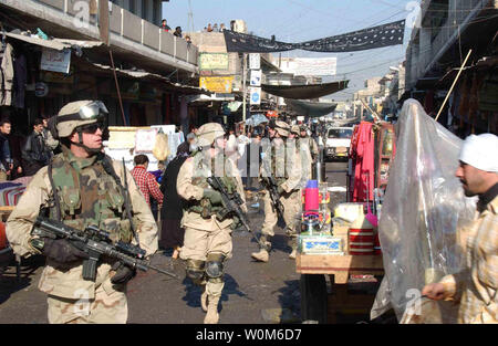 U.S. Army soldiers walk through a market in the Al Sudeek district during a dismounted patrol in Mosul, Iraq, on Jan. 9, 2005.  The soldiers are assigned to Bravo Company, 2nd Battalion, 325th Parachute Infantry Regiment, attached to Task Force Tacoma.  (UPI Photo/ Adam Sanders/Army) - Stock Photo