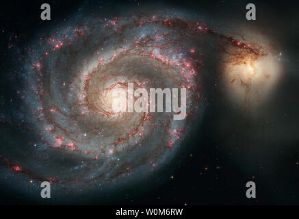 A Hubble photograph of the well-known spiral galaxy M51 showcases a spiral galaxy's classic features, from its curving arms, where newborn stars reside, to its yellowish central core, a home for older stars.  The image was one of two released for the 15th anniversary of the Hubble Space Telescope April 25, 2005.   Fifteen years after being placed into Earth-orbit on Arpil 25, 1990 by NASA, the versatile telescope continues to deliver exciting new science.   (UPI Photo/Hubble/NASA) - Stock Photo