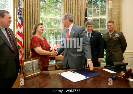 President George W. Bush shakes the hand of Janet Norwood after signing into law H.R. 1001, the Naming of the Sergeant Byron W. Borwood Post Office Building, designating the US Postal Service facility in Pflugerville, Texas, in honor of the 25-year-old Marine who died in combat, in the White House on July 21, 2001.  Joining Mrs. Norwood and the President for the signing are, from left:  Bill Norwood, husband and father; Congressman Michael McCaul, R-Texas, and First Lt. T. Ryan Sparks, 3rd Battalion, 1st Marines.    (UPI Photo/Eric Draper/White House) - Stock Photo