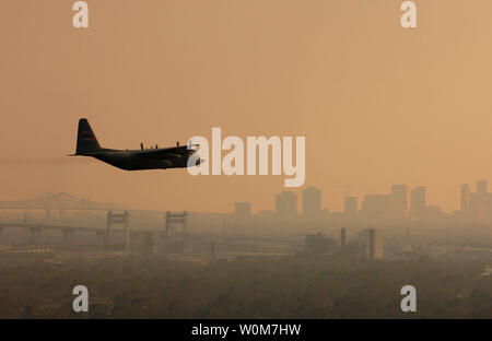 A U.S. Air Force Reserve C-130 Hercules from the 910th Airlift Wing, Youngstown Air Reserve Station, Ohio, sprays Dibrom, a pesticide approved by the U.S. Environmental Protection Agency, over New Orleans, LA, Sept. 13, 2005.  In coordination with the Federal Emergency Management Agency and the Centers for Disease Control, the C-130 crew plans to spray the area of New Orleans first, then work other affected Gulf Coast areas as required.  The insects which will be targeted are primarily mosquitoes and filth flies which are capable of transmitting diseases such as Malaria, West Nile Virus, and v - Stock Photo