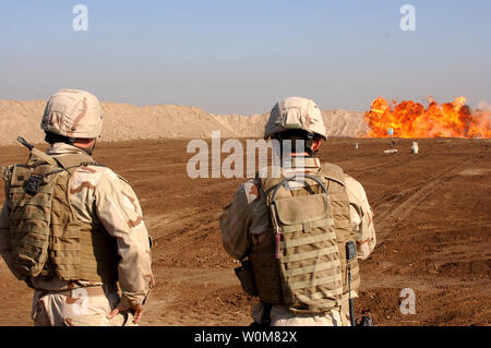 U.S. Navy Lt. Robert Marsh and Petty Officer 2nd Class Michael Piccone, detonate a test explosion at a range in Ad Diwaniyah, Iraq on January 5, 2006. The sailors are assigned to Explosive Ordnance Disposal Mobile Unit 11, Detatchment 11, Woodby Island, Wash.   (UPI Photo/Timothy J. Villareal/Army) - Stock Photo