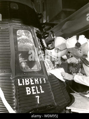 Astronaut Gus Grissom climbs into 'Liberty Bell 7' spacecraft before launch on the morning of July 21, 1961. Astronaut John Glenn, Grissom's back up, helps him into the capsule. A problem with the hatch led Grissom's capsule to sink after splashdown. It was salvaged from the Atlantic Ocean in 1999. Grissom's suborbital flight on a Mercury-Redstone rocket was the second manned U.S. spaceflight. Glenn followed him a month later with the first orbital flight by an American. (UPI Photo/NASA) - Stock Photo