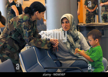 U.S. Air Force Staff Sgt Margaret Alawi-Westphal, 435th Dental Squadron, speaks with Zarnab Hage about her journey from Lebanon to the Air Mobility Command Passenger Terminal, Ramstein Air Base, Germany on July 25, 2006. Zarnab is one of American citizens are being transported back to the continental United States.  (UPI Photo/Julianne Trulson/USAF) - Stock Photo