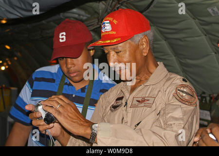 Retired U.S. Air Force Lt. Col., and a member of the Tuskeegee Airmen, Bob Ashby, shows photos to a Civil Air Patrol cadet during an incentive flight on a KC-135 Stratotanker for students in the Civil Air Patrol and the Aviation Careers Education camp being held in Phoenix, Ariz., on  August 1, 2006. (UPI Photo/Joe Zuccaro/USAF) - Stock Photo