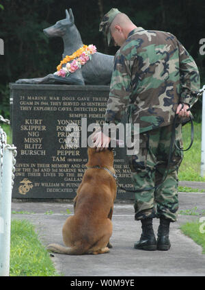 U.S. Navy Petty Officer 2nd Class Blake Soller and his military working dog Rico pay tribute to the National War Dog Cemetery on Naval Base Guam on October 27, 2006.  Soller is a K-9 handler assigned to Naval Security Force Detachment Guam.  This memorial was dedicated in 1998 to the dogs who died helping American soldiers liberate the island of Guam during WWII.  (UPI Photo/John F. Looney/Navy) - Stock Photo