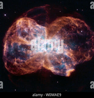 """A brand new image taken with Hubble's Wide Field Planetary Camera 2 shows the planetary nebula NGC 2440 - the chaotic structure of the demise of a star. This image of NGC 2440 shows the colourful """"last hurrah"""" of a star like our Sun. The star is ending its life by casting off its outer layers of gas, which formed a cocoon around the star's remaining core. Ultraviolet light from the dying star makes the material glow. The burned-out star, called a white dwarf, is the white dot in the center.  Photo released February 13, 2007.  (UPI Photo/NASA/ESA/K.Noll-STScI) - Stock Photo"""