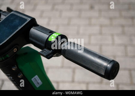 Berlin, Germany - June, 2019: Electric scooter , escooter or e-scooter of the ride sharing company LIME on sidewalk in Berlin, Germany - Stock Photo