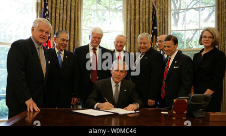 U.S. President George W. Bush signs H.R. 5715 into law in the Oval Office of the White House in Washington on May 7, 2008. The bill, 'Ensuring Continued Access to Student Loans Act of 2008,' is designed to provide continued availability of access to the Federal student loan program for students and families. Looking on are (L to R) Sen. Ted Kennedy, (D-MA); Rep. Ruben Hinojosa (D-TX); Rep. George Miller )D-CA); Rep. Buck McKeon (R-CA); Sen. Mike Enzi, (R-WY); Secretary of Treasury Hank Paulson; Rep. Ric Keller (R-FL), and Secretary of Education Margaret Spellings. (UPI Photo/Chris Greenberg) - Stock Photo
