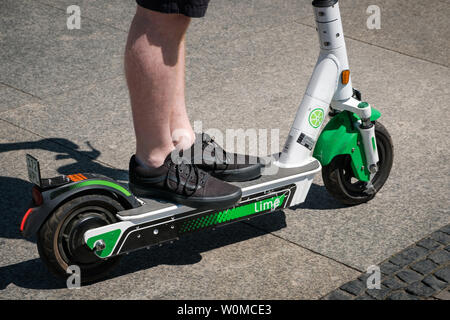 Berlin, Germany - June, 2019: Man riding an electric scooter , escooter or e-scooter of the ride sharing company LIME on sidewalk in Berlin, Germany - Stock Photo