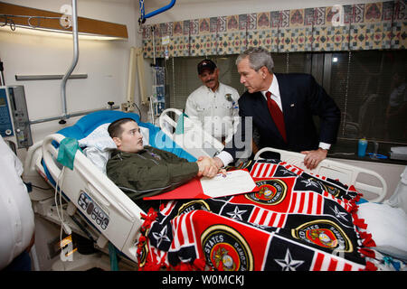 U.S. President George W. Bush shakes hands with U.S. Marine Corps Lance Cpl. Justin Rokohl of Orange Grove, Texas, after awarding him a Purple Heart medal at the Walter Reed National Military Medical Center in Bethesda, Maryland on July 3, 2008. Rokohl's father, John, looks on. (UPI Photo/Eric Draper/White House Press Office) - Stock Photo