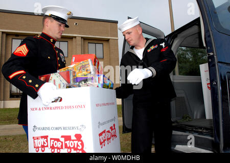 Marine Corps Sergeant Jeffrey Kellum hands a box of donated toys to Hospital Corpsman 2nd Class Christopher Long as part of the 'Toys for Tots' program in Gulfport, Mississippi, December 18, 2008. The toys, donated by Naval Mobile Construction Battalion (NMCB) 11, will be given to less fortunate  children in the Gulfport/Biloxi area. (UPI Photo/Erick S. Holmes/U.S. Navy) - Stock Photo