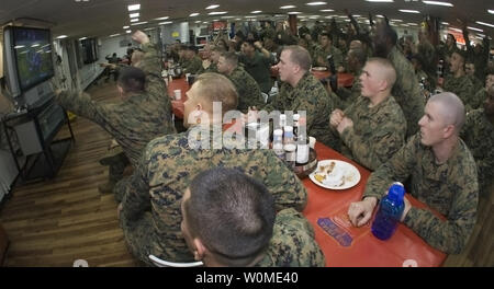 U.S. Sailors and Marines, on the mess deck of forward-deployed amphibious assault ship USS Essex (LHD 2), react as the Pittsburgh Steelers score against the Arizona Cardinals late in the fourth quarter to win Super Bowl XLIII, in the South China Sea on February 2, 2009. (UPI Photo/Gabriel S. Weber/U.S. Navy) - Stock Photo