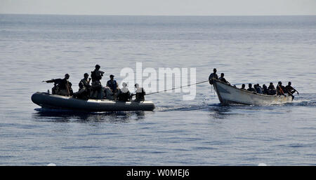 Members of the visit, board, search, and seizure team from the guided-missile cruiser USS Lake Champlain (CG 57) tow a disabled skiff carrying 52 Somali migrants in the Gulf of Aden on May 24, 2009. The skiff was spotted in distress by Lake Champlain helicopter pilots while patrolling the area.    (UPI Photo/Daniel Barker/U.S. Navy) - Stock Photo