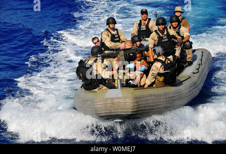 Members of the visit, board, search, and seizure team transport Somali migrant children to the guided-missile cruiser USS Lake Champlain (CG 57) after being rescued from a disabled skiff in the Gulf of Aden on May 24, 2009. The skiff, originally ferrying 52 passengers, was spotted in distress by Lake Champlain helicopter pilots while patrolling the area.   (UPI Photo/Daniel Barker/U.S. Navy) - Stock Photo