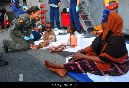 Lt. Katherine Scholz, the air operations officer for Helicopter Anti-Submarine Squadron Light (HSL) 45, detachment Four, assists Somali migrants aboard the guided-missile cruiser USS Lake Champlain (CG 57) after their rescue from a disabled skiff in the Gulf of Aden on May 24, 2009. The skiff, originally ferrying 52 passengers, was spotted in distress by Lake Champlain helicopter pilots while patrolling the area  (UPI Photo/Daniel Barker/U.S. Navy) - Stock Photo