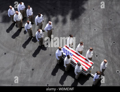 U.S. Navy chief petty officers assigned to Carrier Air Wing 7 act as pallbearers for Command Master Chief Jeffrey J. Garber during a departure ceremony aboard the aircraft carrier USS Dwight D. Eisenhower while under way in the Arabian Sea on June 22, 2009. Garber, the command master chief of Carrier Air Wing 7, died of natural causes while deployed aboard the aircraft carrier on June 20, 2009. (UPI Photo/Jon Dasbach/U.S. Navy) - Stock Photo