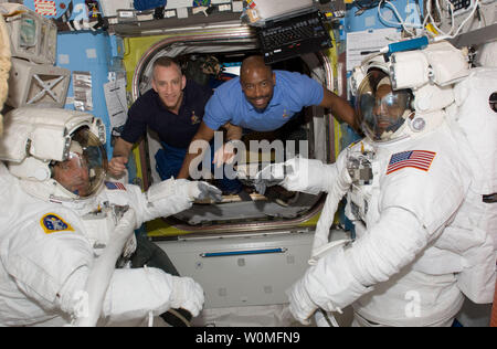 This NASA photo shows astronauts Mike Foreman (left) and Robert L. Satcher Jr. (right), STS-129 mission specialists, as they prepare for their flight day four space walk, as astronauts Charles O. Hobaugh (second left), commander, and Leland Melvin, mission specialist, stay close at hand to assist them, November 19, 2009.   UPI/NASA - Stock Photo