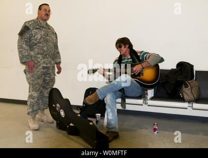 U.S. Navy Chief Petty Officer Craig Strawser sings a song with singer Billy Ray Cyrus during a visit to the International Security Assistance Force Joint Command at North Kabul International Airport Military Facility in Afghanistan, as part of a USO Holiday Troop Visit on December 14, 2009. UPI/Ryan Tabios/U.S. Navy - Stock Photo