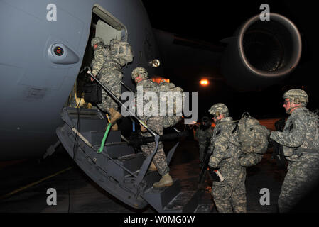 A group of Soldiers from Charlie Company, 2nd Battalion, 22nd Infantry Regiment of the 10th Mountain Division's 1st Brigade Combat Team, board a C-17 transport plane to depart Fort Drum, New York, for Afghanistan, on January 9. 'Triple Deuce' is the first of six battalions from the 1st BCT that are deploying with the troop surge in support of Operation Enduring Freedom. UPI/John Queen/U.S. Army - Stock Photo
