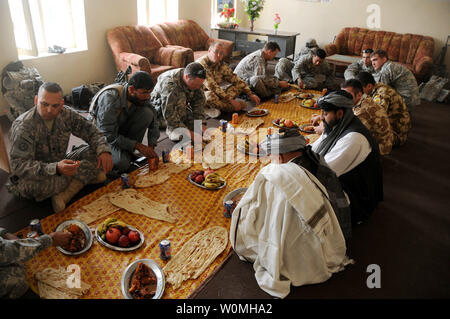 U.S. and Romanian soldiers eat lunch at the Shah Joy District Center near Highway 1 in the Zabul province of Afghanistan Oct. 29, 2010. The U.S. Soldiers were from Charlie Company, 1st Battalion, 4th Infantry Regiment.    UPI/Joshua Grenier/U.S. Army - Stock Photo