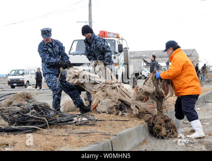 Sailors assigned to Naval Air Facility Misawa carries debris to a dumpsite during a cleanup effort at the Misawa Fishing Port, in Misawa, Japan, March 14, 2011. More than 90 Sailors from Naval Air Facility Misawa volunteered in the relief effort, assisting Misawa City employees and members of the community following the 8.9 magnitude earthquake and tsunami that devastated the country. UPI/Devon Dow/U.S. Navy. - Stock Photo