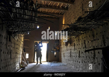 US Army Sgt. 1st Class Jeffrey Cesaitis secures a grape drying house before members of Provincial Reconstruction Team Zabul and the U.S. Department of Agriculture enter during a visit to a village near the city of Qalat, Zabul province, Afghanistan, May 8, 2011. UPI/DOD - Stock Photo
